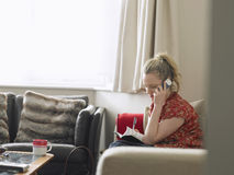 Woman With Diary Using Mobile Phone At Home Royalty Free Stock Photo