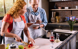 Woman dictating ingredients to man. Listen carefully. Wise good looking women dictating ingredients to her men while cutting vegetables Stock Images