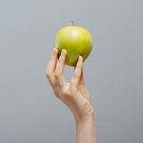 Woman on diet with an apple in the hand against gray background Royalty Free Stock Photography