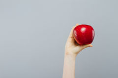 Woman on diet with an apple in the hand against gray background Royalty Free Stock Images