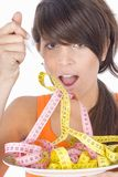 Woman diet eating a tape measures Royalty Free Stock Photography