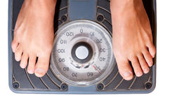 Woman on diet. Scale isolated. Feet on a bathroom scale isolated on white. Woman on diet steped on scale Royalty Free Stock Images