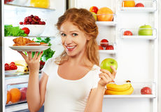 Woman on diet to choose between healthy and unhealthy food near. Woman on a diet to choose between healthy and unhealthy food near refrigerator royalty free stock image