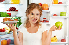 Woman on  diet to choose between healthy and unhealthy food near. Woman on a diet to choose between healthy and unhealthy food near refrigerator Stock Images