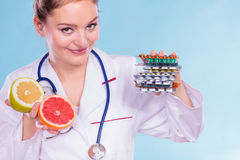 Woman with diet weight loss pills and grapefruits. Royalty Free Stock Images