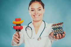 Woman with diet weight loss pills and vegetables. Stock Image