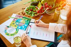 Woman dietitian in medical uniform with tape measure working on a diet plan sitting with different healthy food ingredients in the