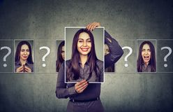 Woman with different portrait photos. Young woman having split personality while posing with photos of different emotions Royalty Free Stock Photo
