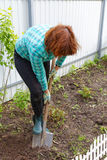 Woman digging the ground with a shovel. On a close-up of a garden royalty free stock photos