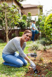 Woman digging hole. Cheerful women digging a hole before planting with boyfriend on background watering garden Stock Image