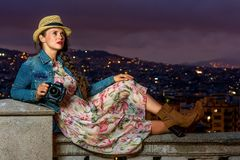 Woman with digital camera looking into the distance. Perfect evening with stunning view. stylish woman in long dress and straw hat against cityscape of Barcelona Stock Photos