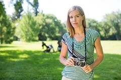 Woman With Digital Camera In Park Stock Photo