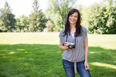 Woman With Digital Camera In Park Stock Photography