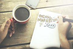 Woman and digital marketing. Woman hand writing in notebook Marketing on wooden table stock photo