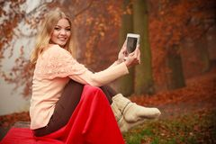 Woman with digital tablet in autumn park. Autumn time people outside. Beautiful woman with digital tablet. Young lady sitting on bench and wearing autumnal Stock Photography