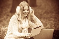 Woman with digital tablet in autumn park. Autumn time people outside. Beautiful woman with digital tablet. Young lady sitting on bench and wearing autumnal Royalty Free Stock Photo
