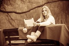 Woman with digital tablet in autumn park. Autumn time people outside. Blonde woman with digital tablet. Young lady sitting on bench and wearing autumnal clothing Royalty Free Stock Photos