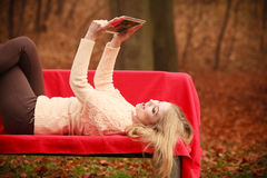 Woman with digital tablet in autumn park. Autumn time people outside. Beautiful woman with digital tablet. Young lady sitting on bench and wearing autumnal Stock Photos
