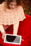 Woman with digital tablet in autumn park. Autumn time people outside. Beautiful woman with digital tablet. Young lady sitting on bench and wearing autumnal Royalty Free Stock Photography