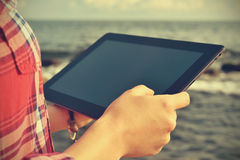 Woman with digital tablet. At beach. Vintage photo Royalty Free Stock Photos