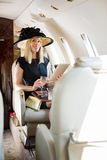Woman With Digital Tablet And Drink Glass In. Portrait of rich confident woman with digital tablet and drink glass sitting in private jet Stock Photo