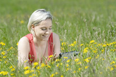 Woman with digital tablet. Happy young blond woman with digital tablet on flower meadow Stock Photography