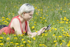 Woman with digital tablet. Happy young blond woman with digital tablet on flower meadow Royalty Free Stock Photography
