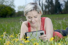 Woman with digital tablet. Happy young blond woman with digital tablet on flower meadow Royalty Free Stock Images