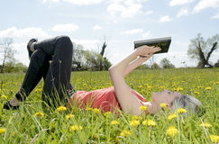 Woman with digital tablet. Happy young blond woman with digital tablet on flower meadow Royalty Free Stock Photos