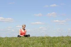Woman with digital tablet. Happy young blond woman with digital tablet on  meadow Royalty Free Stock Image