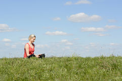 Woman with digital tablet. Happy young blond woman with digital tablet on  meadow Stock Image
