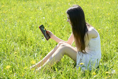 Woman with digital tablet. Happy young woman with digital tablet on  meadow Royalty Free Stock Image