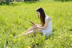 Woman with digital tablet. Happy young woman with digital tablet on  meadow Royalty Free Stock Photo