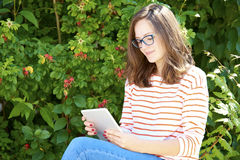 Woman with digital tablet. Portrait of young woman with digital tablet sitting outdoor Stock Image
