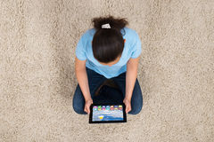 Woman With Digital Tablet Sitting On Carpet Stock Photo