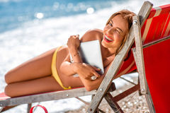 Woman with digital tablet on the sunbed Royalty Free Stock Photo