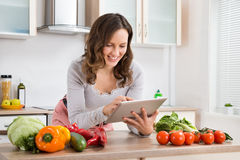 Woman With Digital Tablet And Vegetables Royalty Free Stock Photography