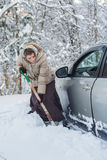 Woman digs car out Royalty Free Stock Photography