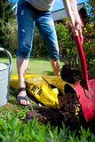 A woman digs soil and soil with a spade shovel and old zinc water can. In close-up Royalty Free Stock Photos