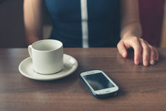 Woman in diner with cup and smartphone Royalty Free Stock Photos