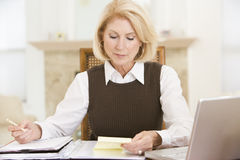 Woman in dining room with laptop and paperwork Royalty Free Stock Photo