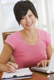 Woman in dining room with laptop smiling stock photos