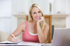 Woman in dining room with laptop smiling Royalty Free Stock Image