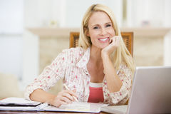 Woman in dining room with laptop smiling Royalty Free Stock Photography