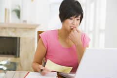 Woman in dining room with laptop thinking.  Royalty Free Stock Photography