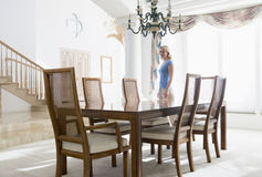 Woman in dining room smiling Royalty Free Stock Image