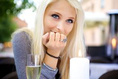 Woman at dining table. Portrait of young beautiful woman sitting at a dining table with a glass of champagne Royalty Free Stock Photo