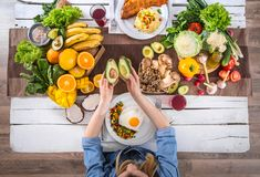 The woman at the dinner table with organic food , the view from the top stock photos