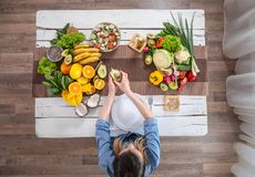 The woman at the dinner table with organic food , the view from the top stock photography