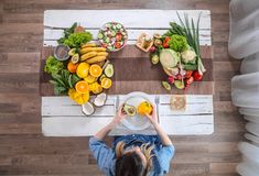 The woman at the dinner table with organic food , the view from the top royalty free stock photos